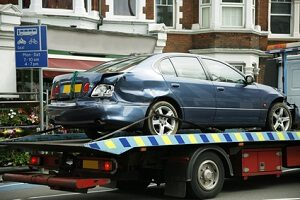 A car that has been damaged in an accident is being towed through Fairfax on a flatbed tow truck.