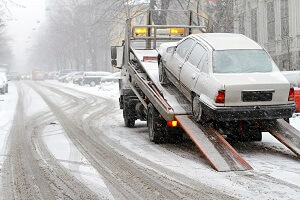 A car has been loaded onto a flatbed tow truck during a snow storm in Fairfax