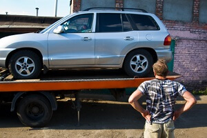 A man is checking out his SUV that has been loaded onto a flatbed tow truck with Fairfax Tow Truck.