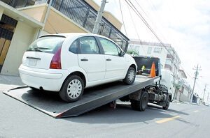 A small white car is being loaded onto a flatbed tow truck from Fairfax Tow Truck
