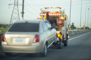 A tow truck is towing a gold colored car down one of the many highways in Fairfax