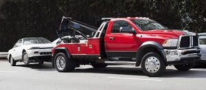 A red tow truck in Fairfax is towing a white car down the street